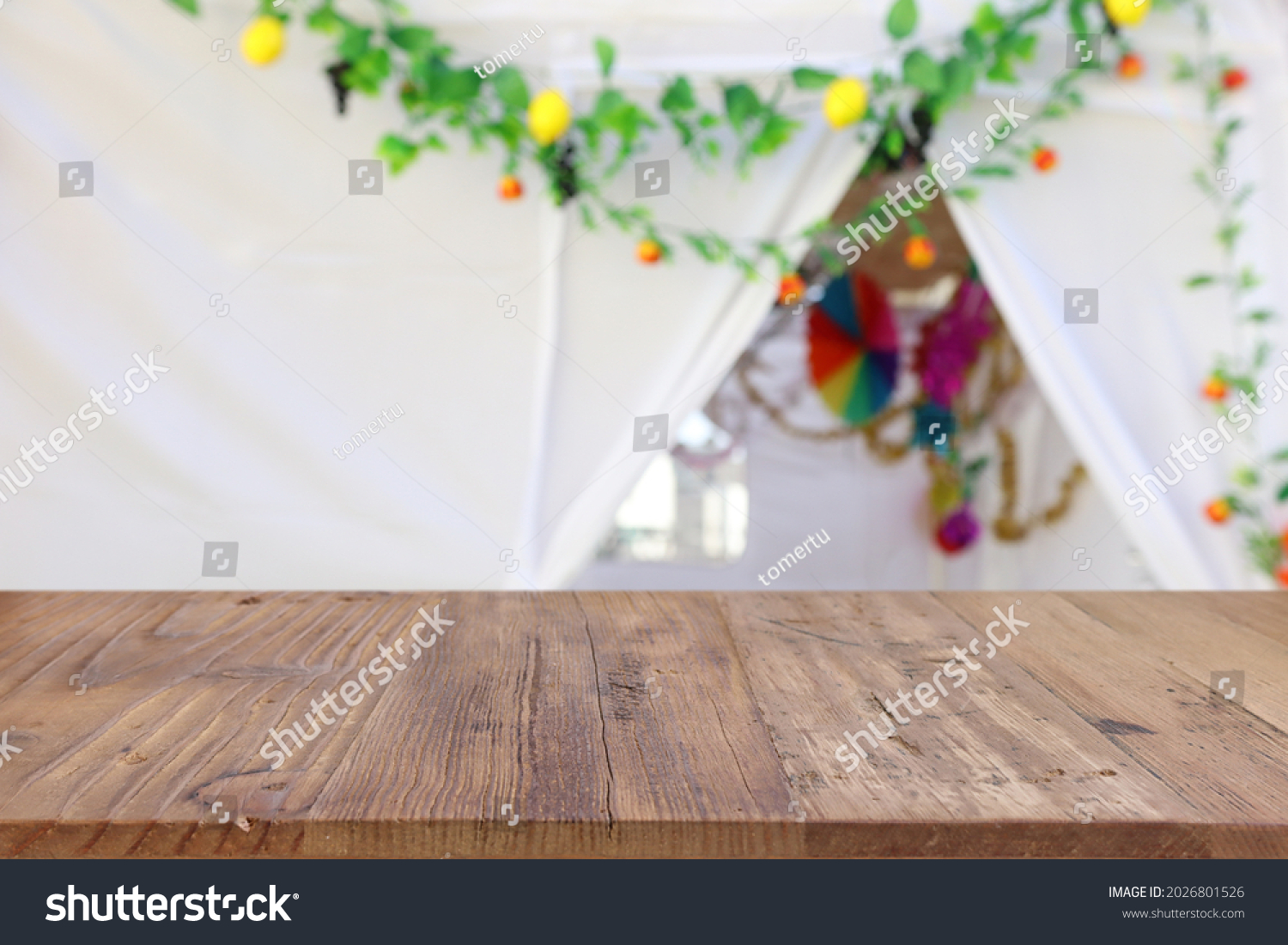 Jewish festival of Sukkot. Traditional succah (hut) with decorations. Empty wooden old table for product display and presentation. #2026801526