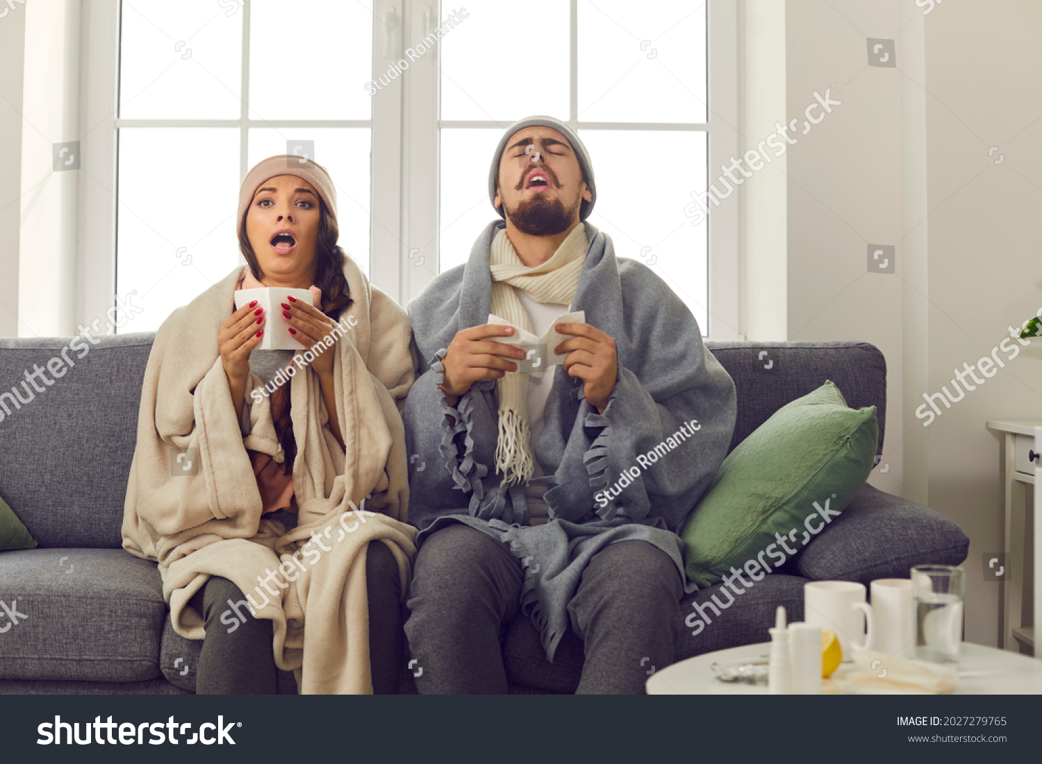 Funny young couple in warm hats, wrapped in blankets, sitting together on couch at home and sneezing in paper tissues. Sick husband and wife suffering from unpleasant symptoms of bad cold or flu virus #2027279765