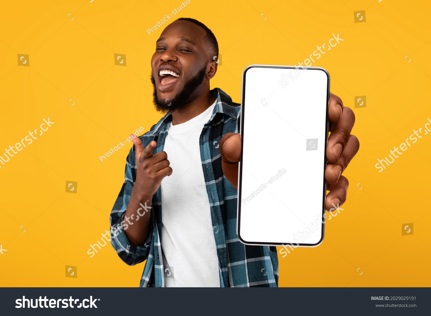 Recommendation. Portrait of excited black guy holding big smartphone with white blank screen in hand, showing close to camera and pointing at device. Gadget with empty free space for mock up, banner #2029029191