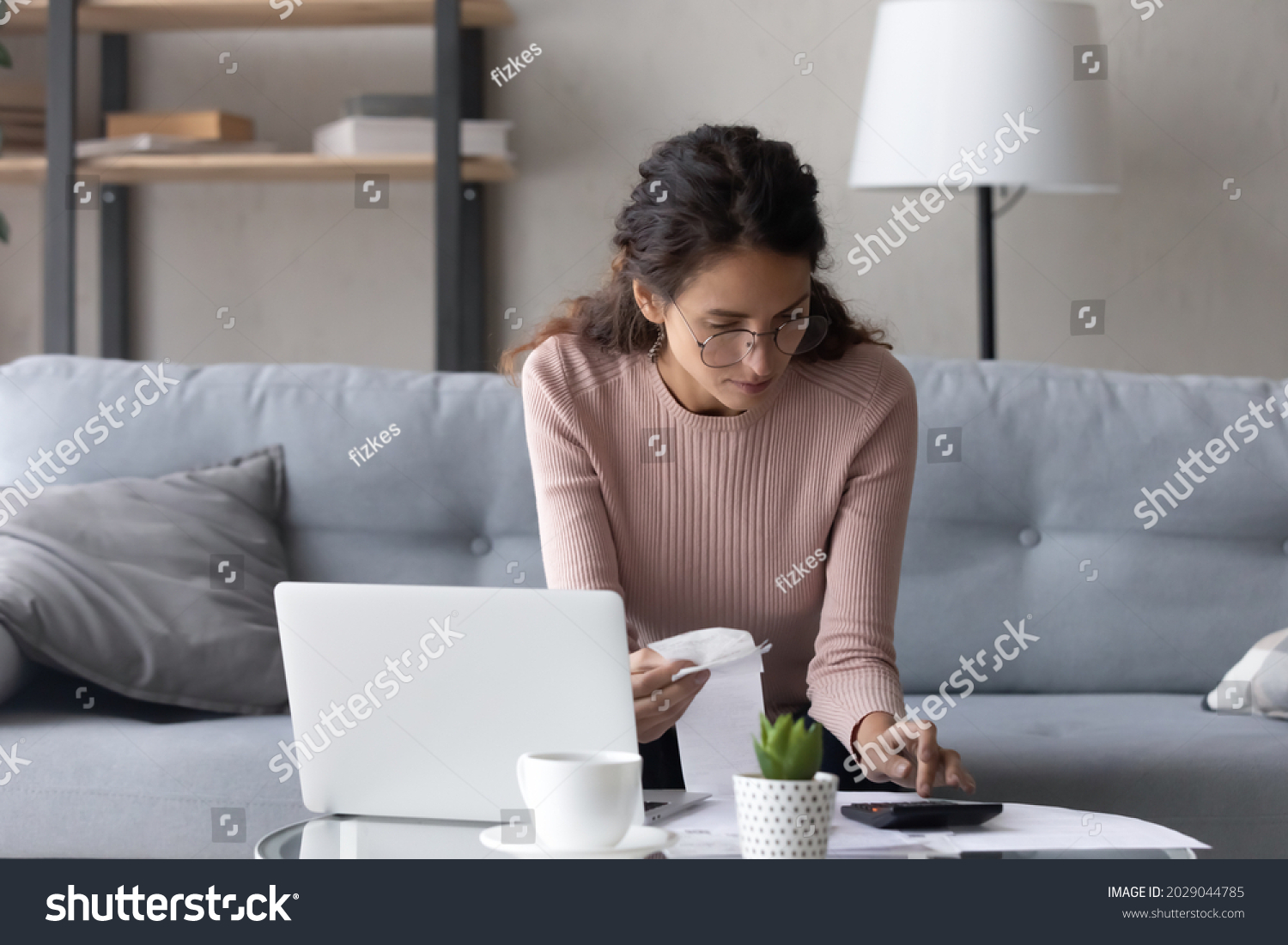 Serious female in glasses paying utility bills, taxes, rental fees use online services e-bank app on laptop. Young woman work from home sit on couch hold paper invoice calculate expenses, make report #2029044785