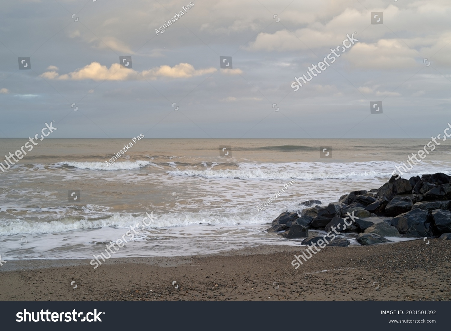 The Irish Sea seascape. Waves, rocks and pebble beach. Evening time just before sunset. Photo taken from the beach in Bray, County Wicklow, Ireland.