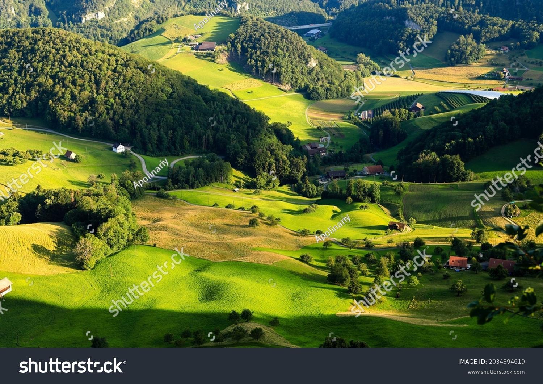 A village in a green mountain valley. Mountain green valley village panorama. Village in mountains. Mountain green hills village #2034394619