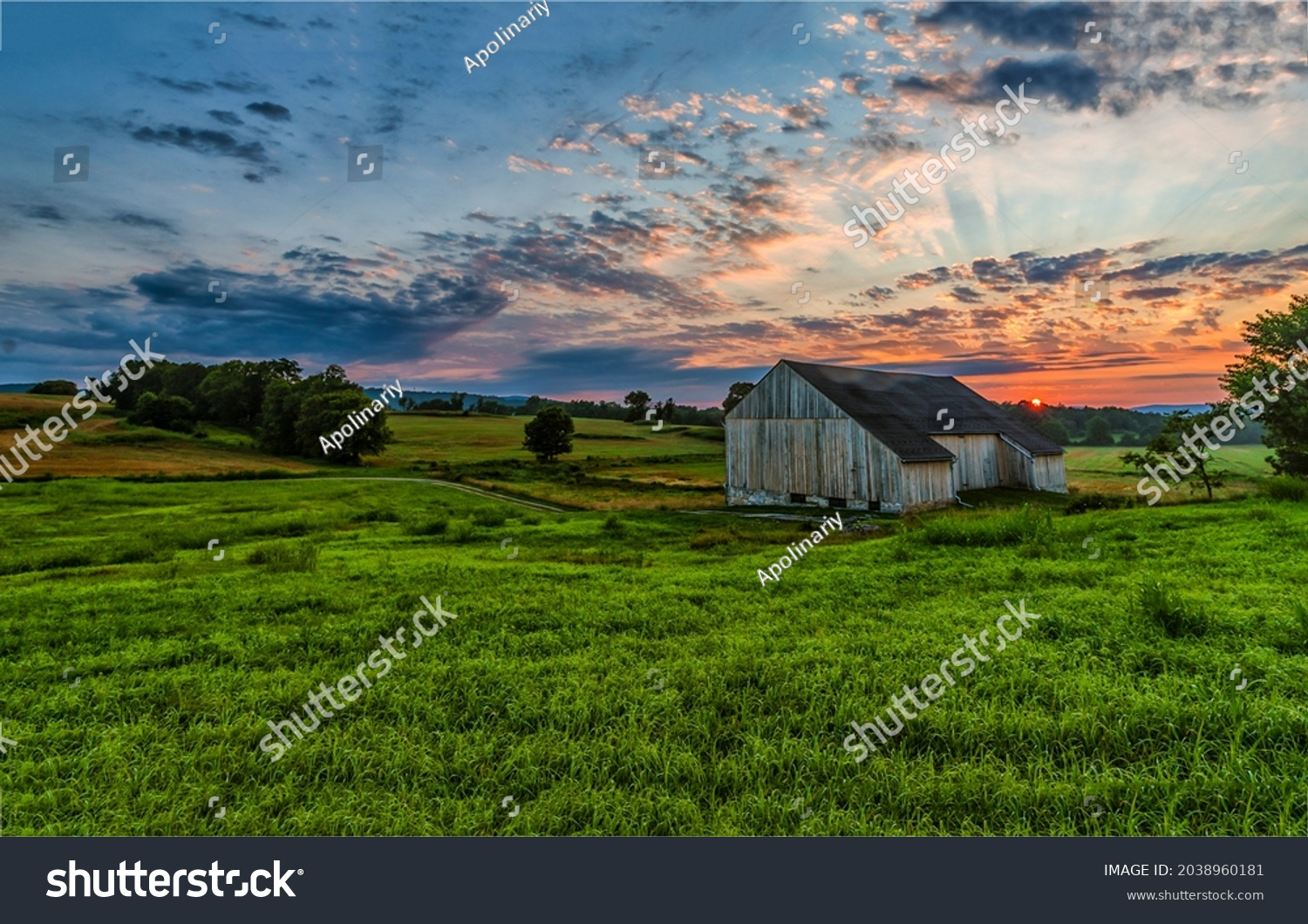 Morning dawn over a farm in a field. Valley farm at dawn. Sunrise over farm field. Early morning farm field at dawn #2038960181