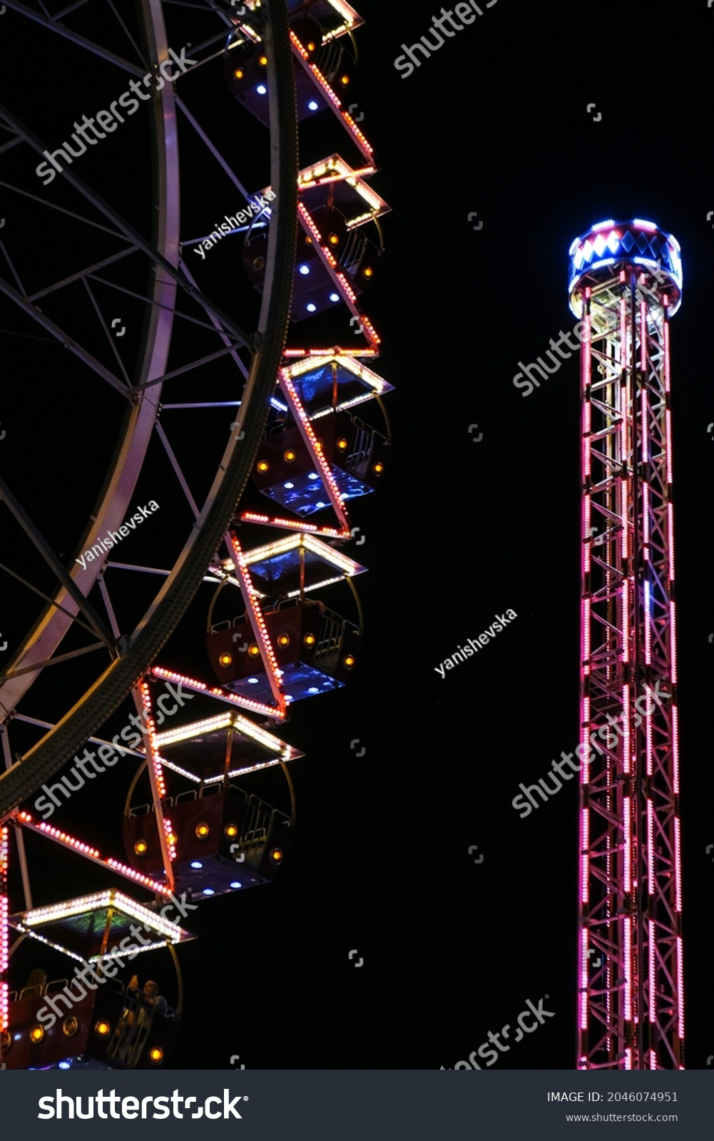Ferris Wheel Lights at Night. Neon colored lights flashing on the Ferris wheel. Amusement park at night. Entertainment and fun. Recreation carousel at carnival. Colorful Ferris wheel #2046074951
