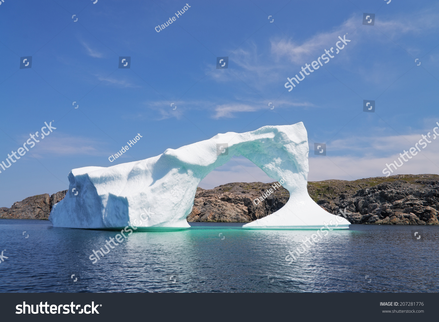 Iceberg in front of a rocky island near Twillingate in Newfoundland and Labrador, Canada