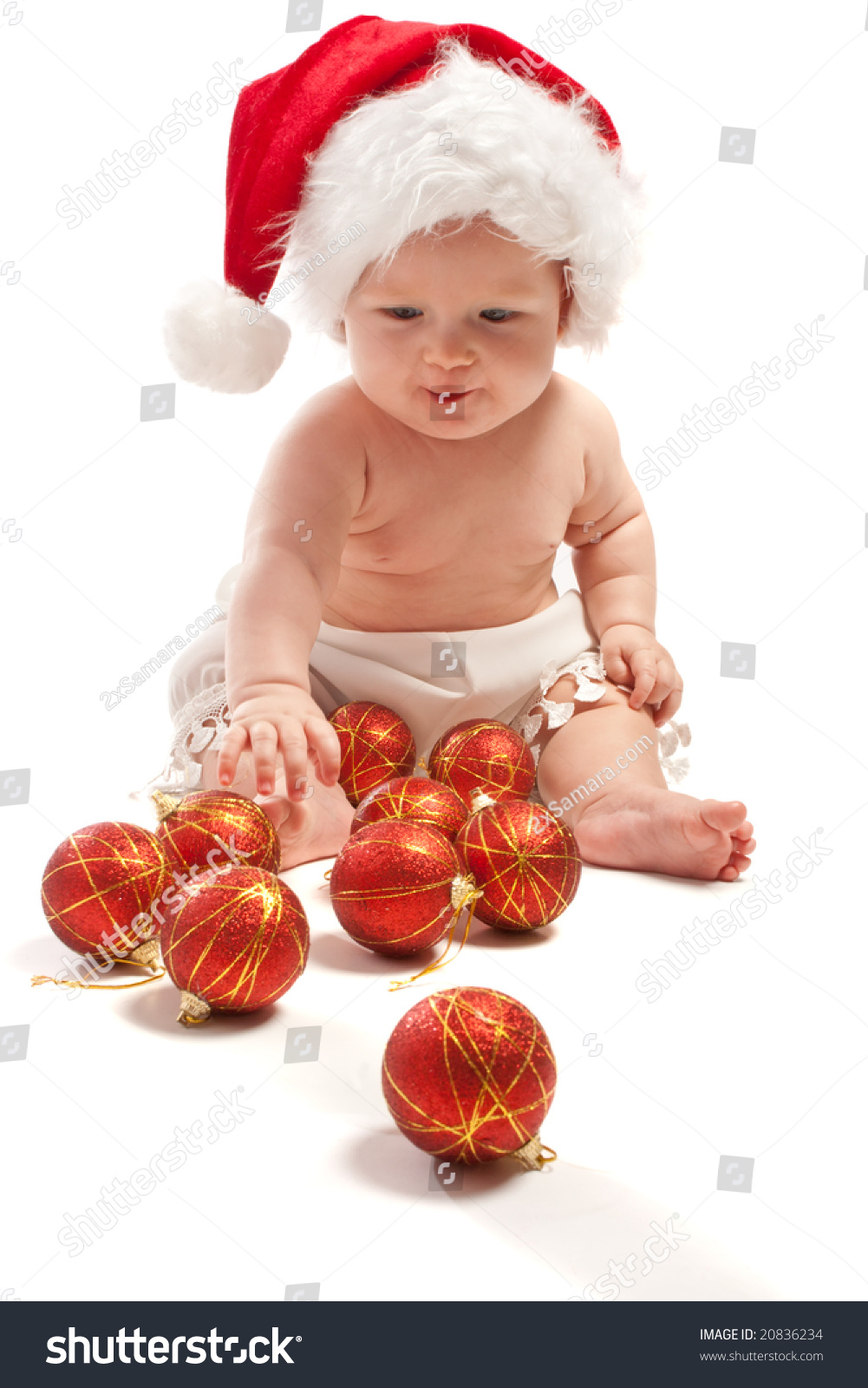 Baby santa hat playing christmas balls stock photo