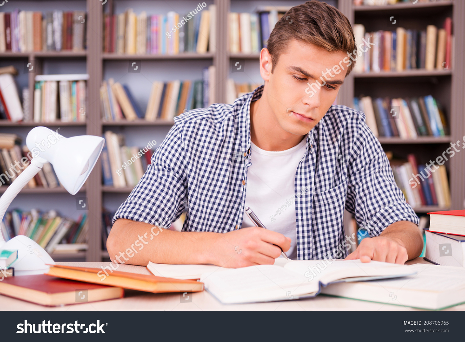 studying hard good grades confident young stock photo  studying hard for good grades confident young man making research while sitting in library