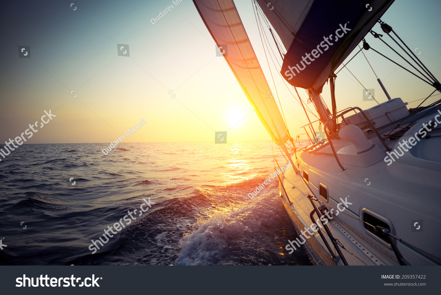 Sail boat gliding in open sea at sunset #209357422