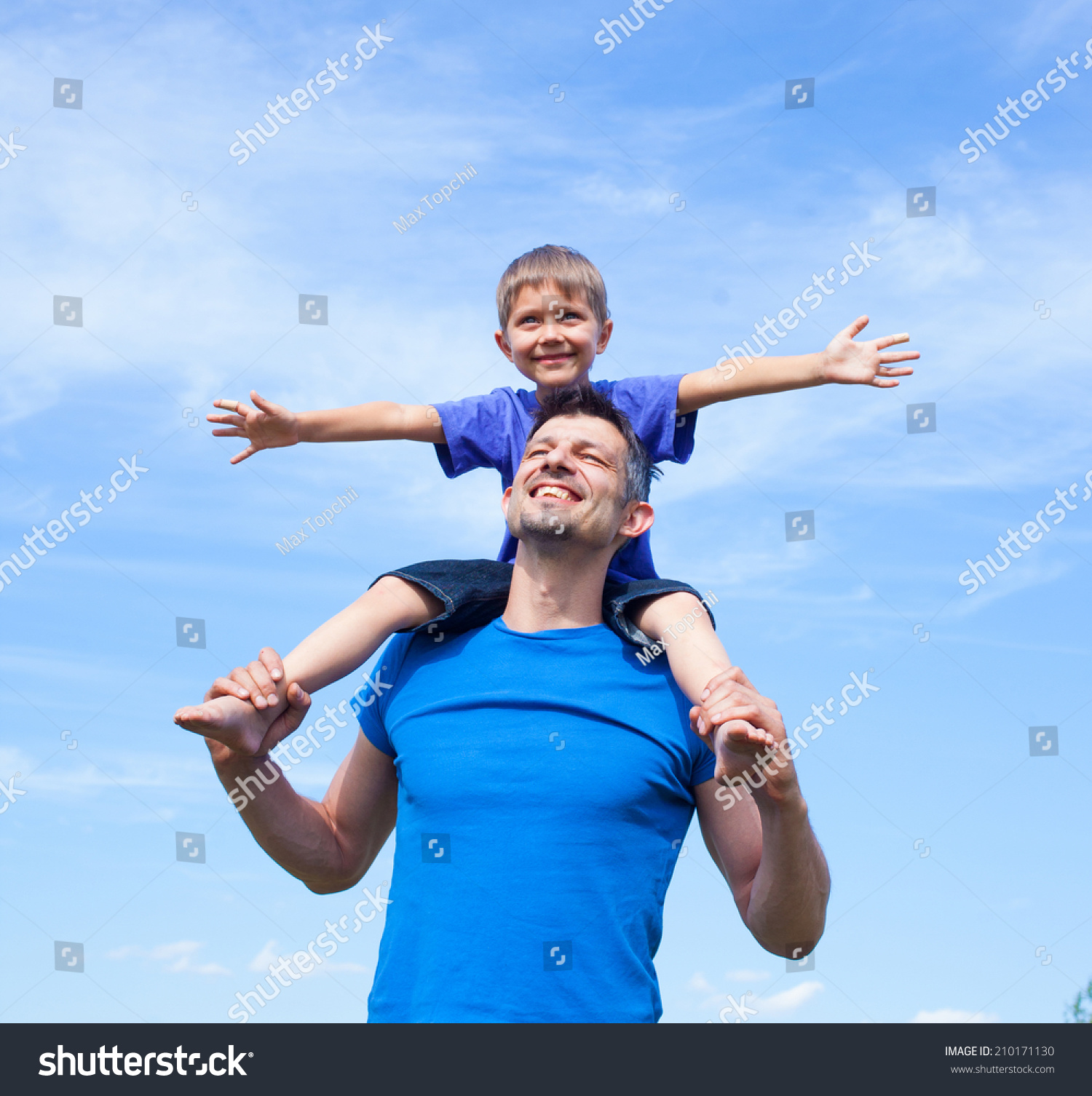 Portrait Of Smiling Father Giving His Son Piggyback Ride