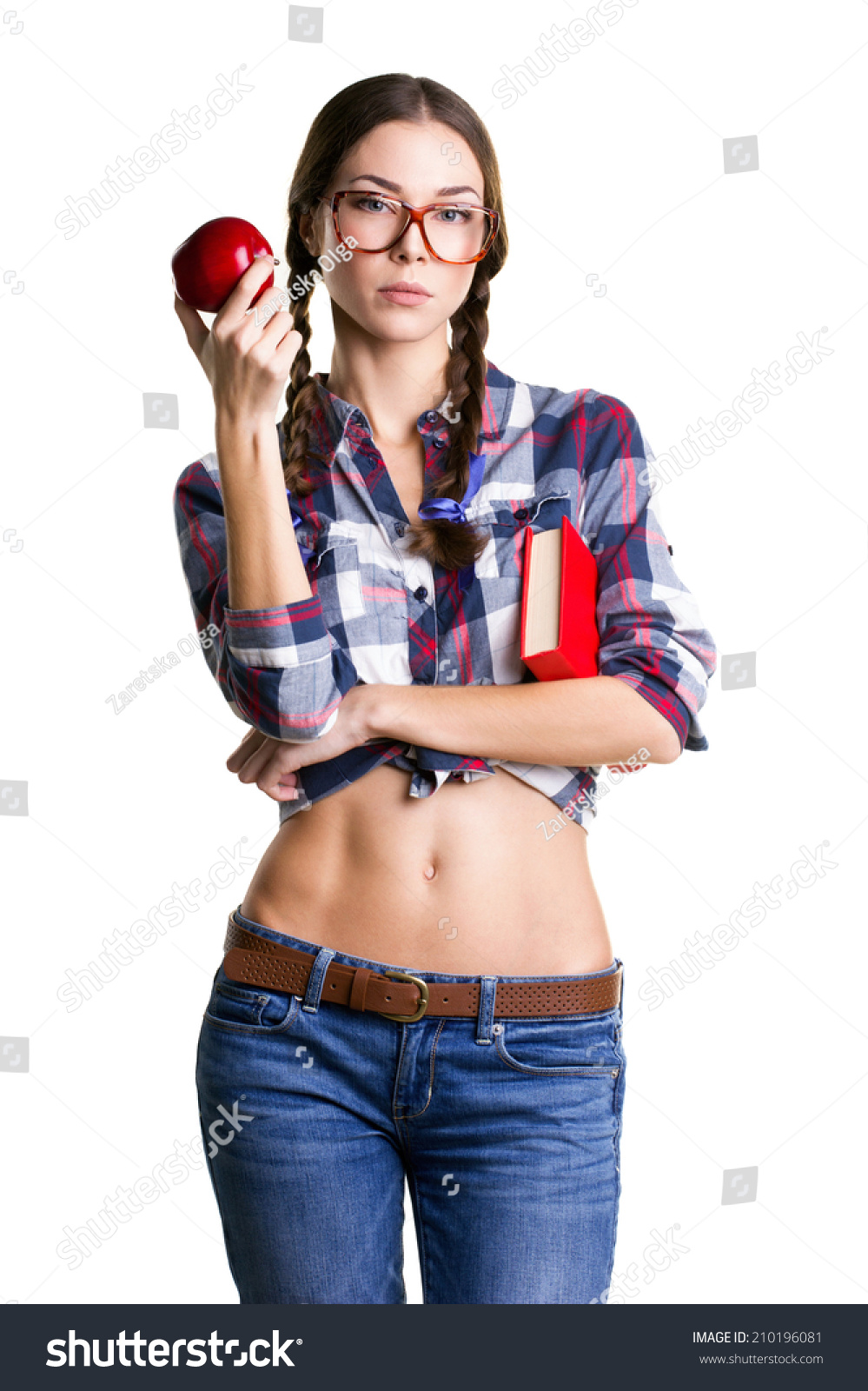 Bely teen smiling teen girl in big glasses, casual clothes and naked belly holding  book and apple