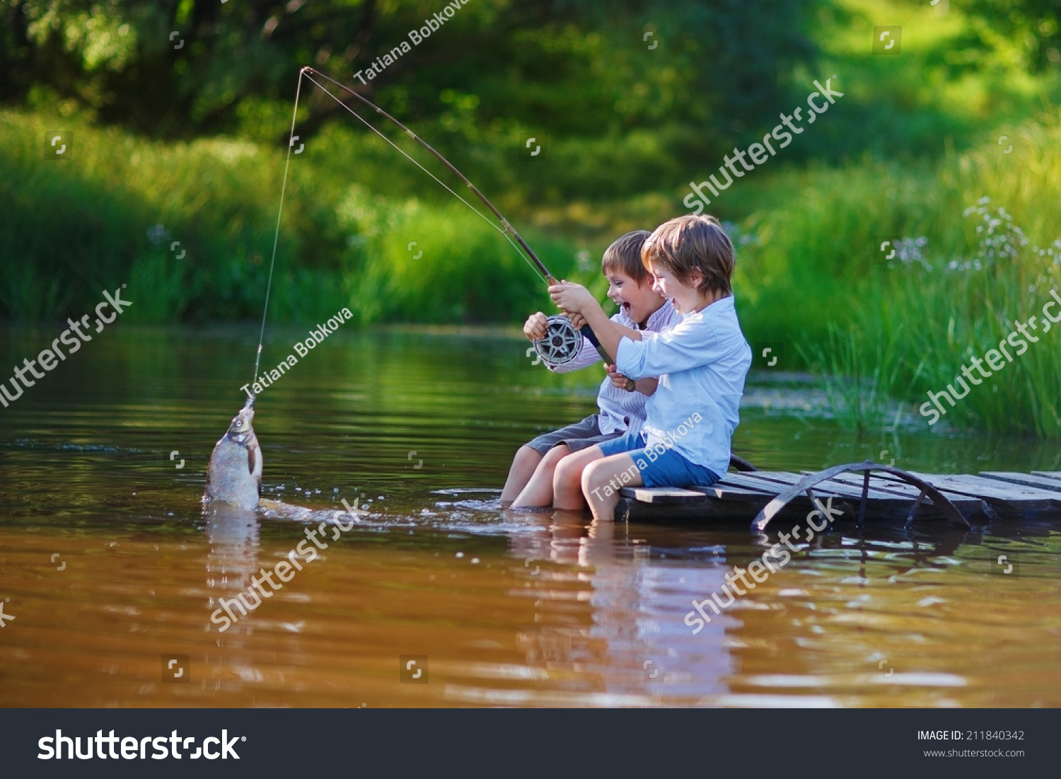 Two young cute boys fishing on a lake in a sunny summer for Little boy fishing