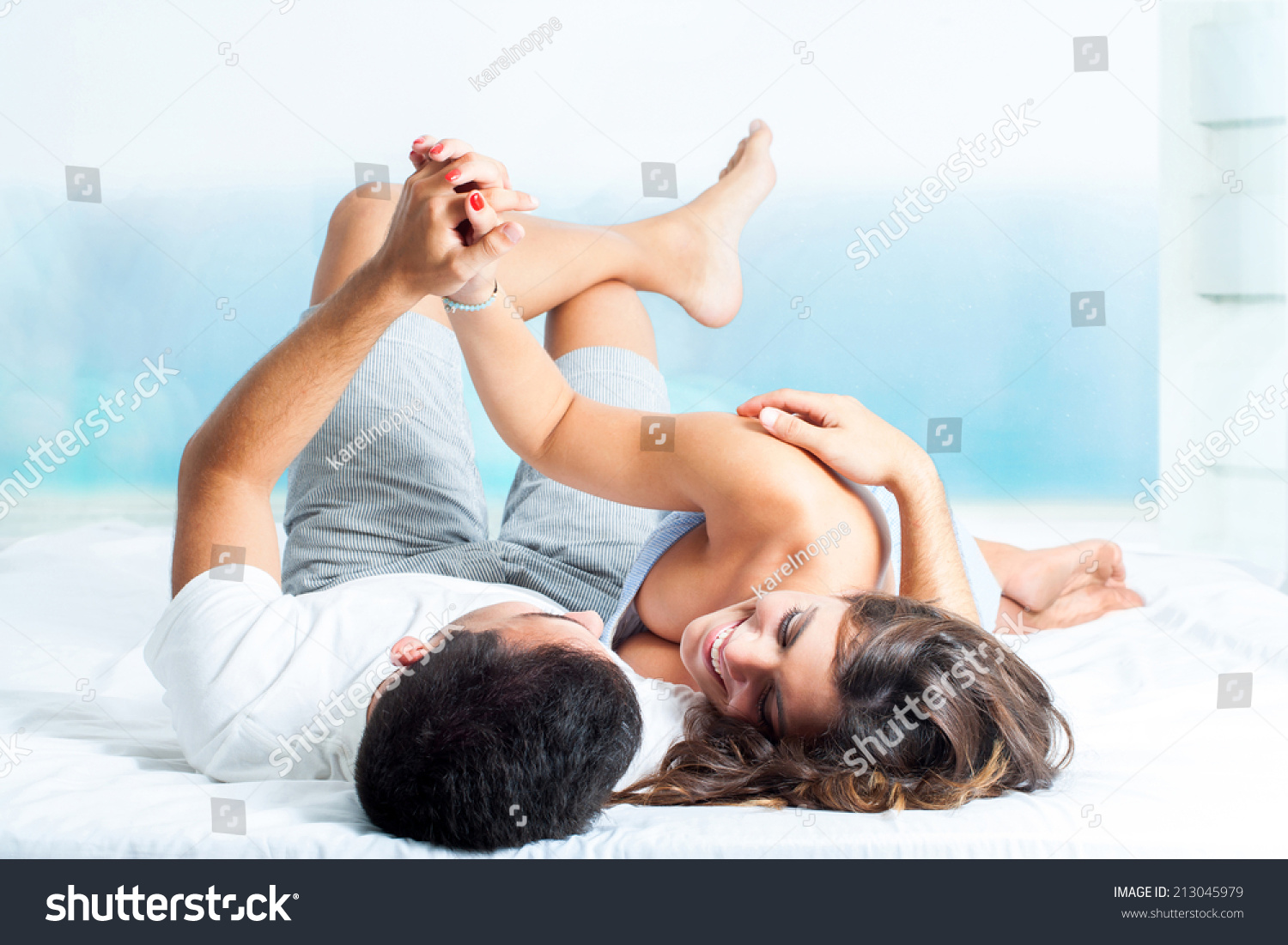young laughing couple laying on bed holding hands stock photo 213045979 shutterstock. Black Bedroom Furniture Sets. Home Design Ideas