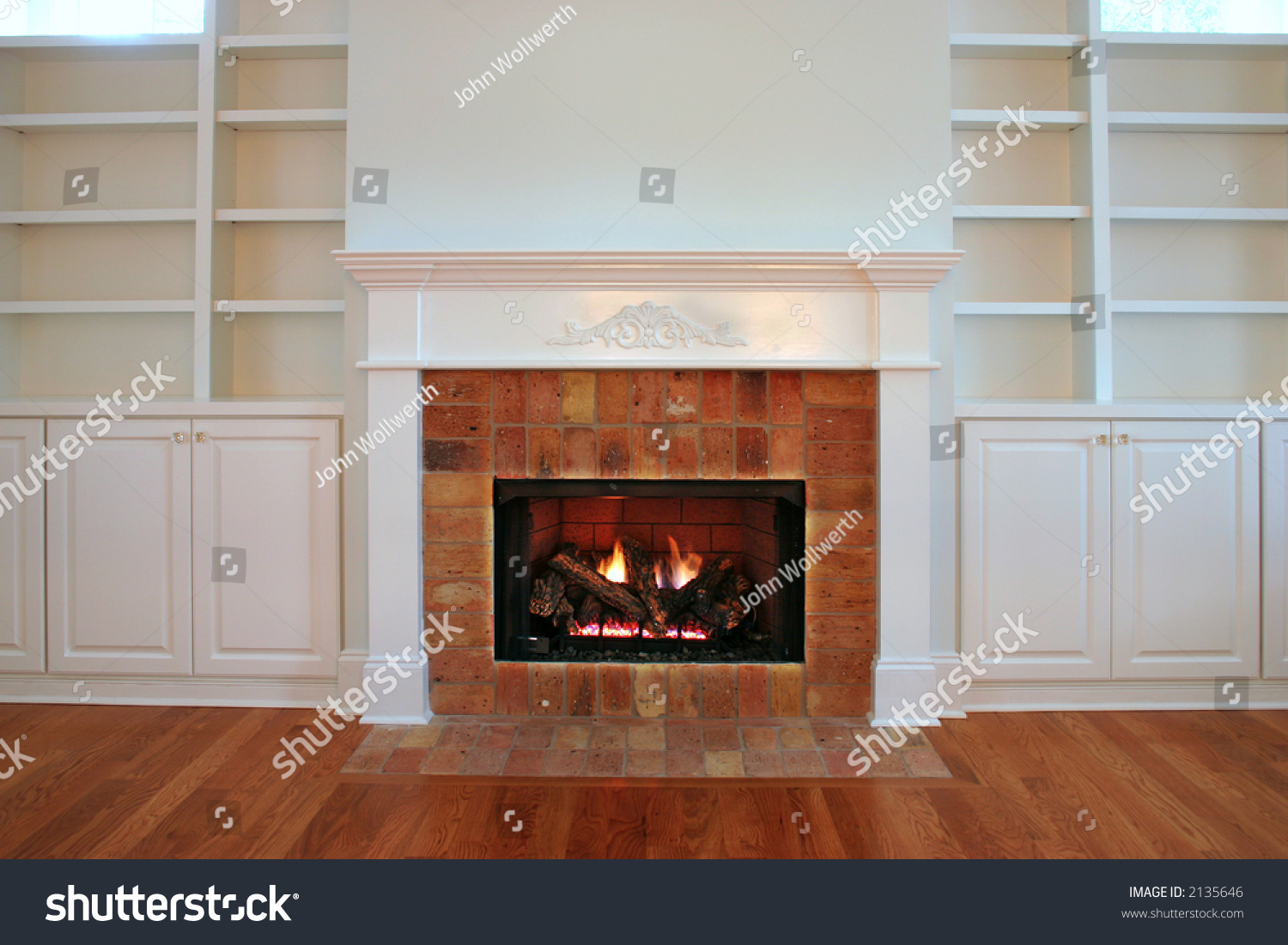 lit fireplace surrounded by built bookshelves stock photo 2135646
