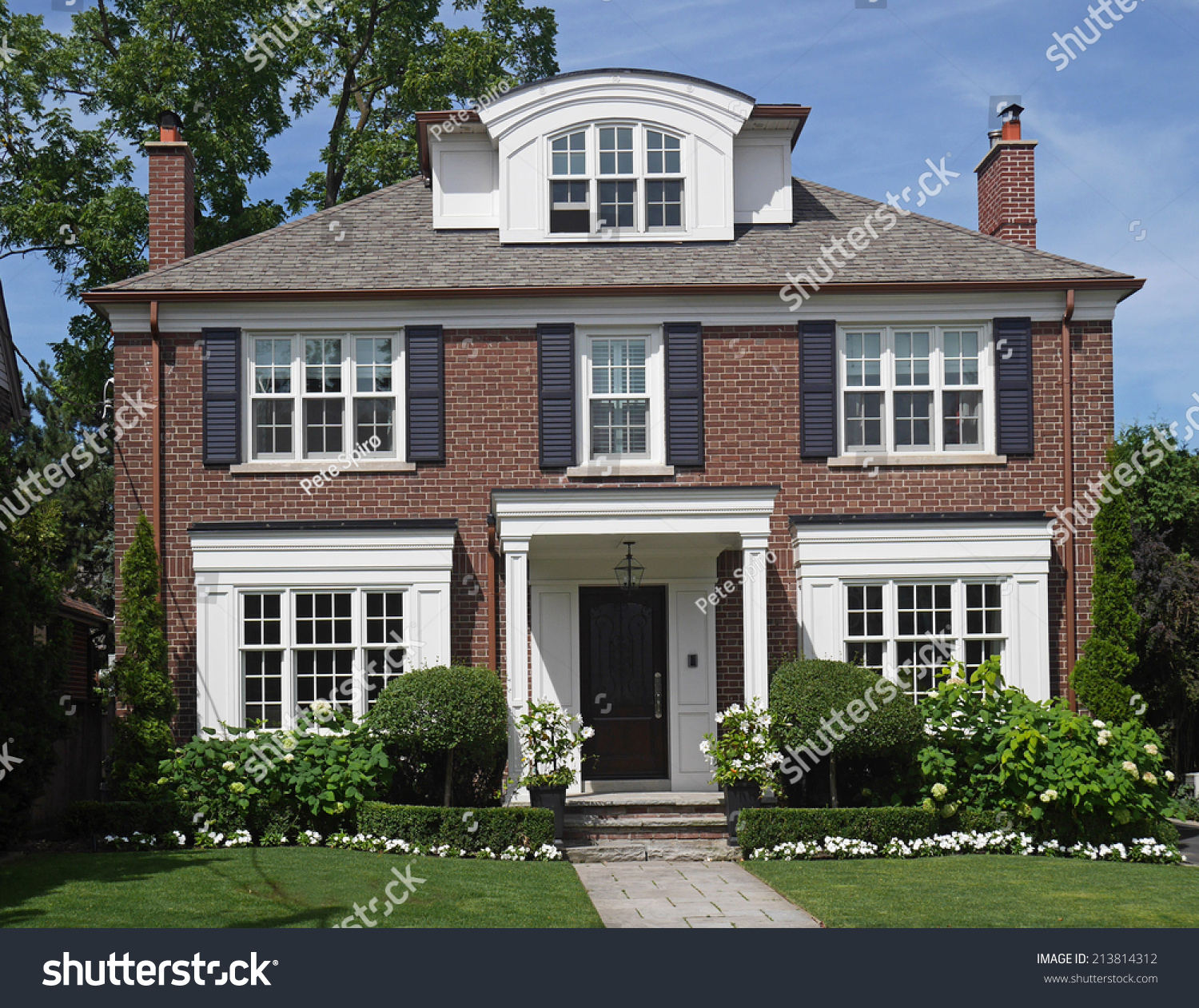 Traditional two story brick house with dormer window stock for Traditional 2 story house