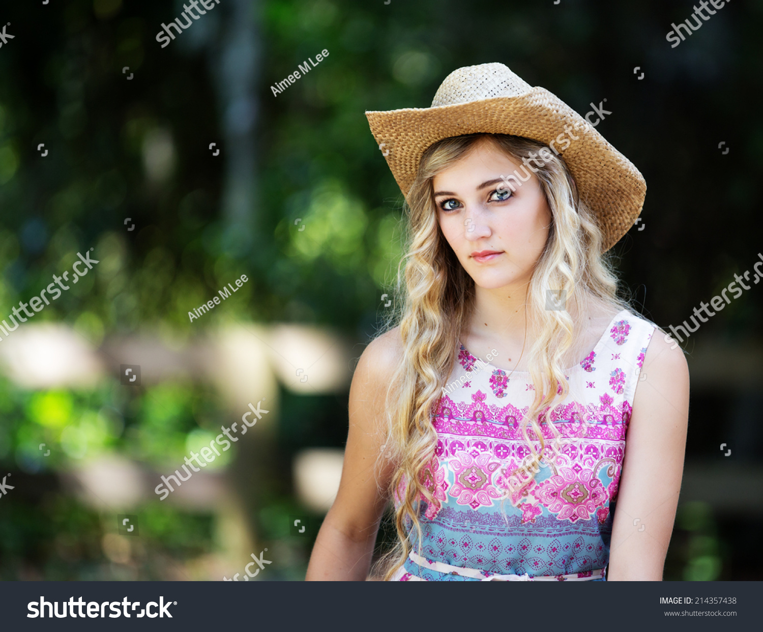 76ca597d639 Portrait of a beautiful country girl with curly blonde hair wearing a cowboy  hat and a