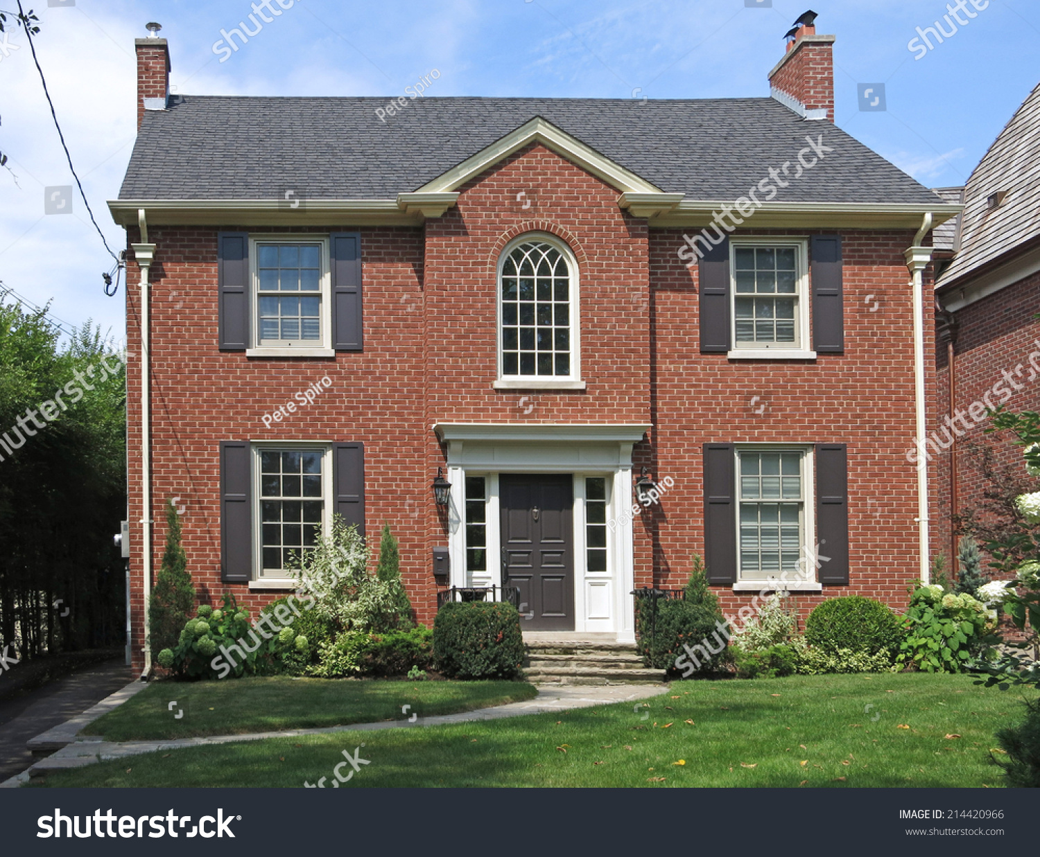 Traditional two story brick house shutters stock photo for Brick traditional homes