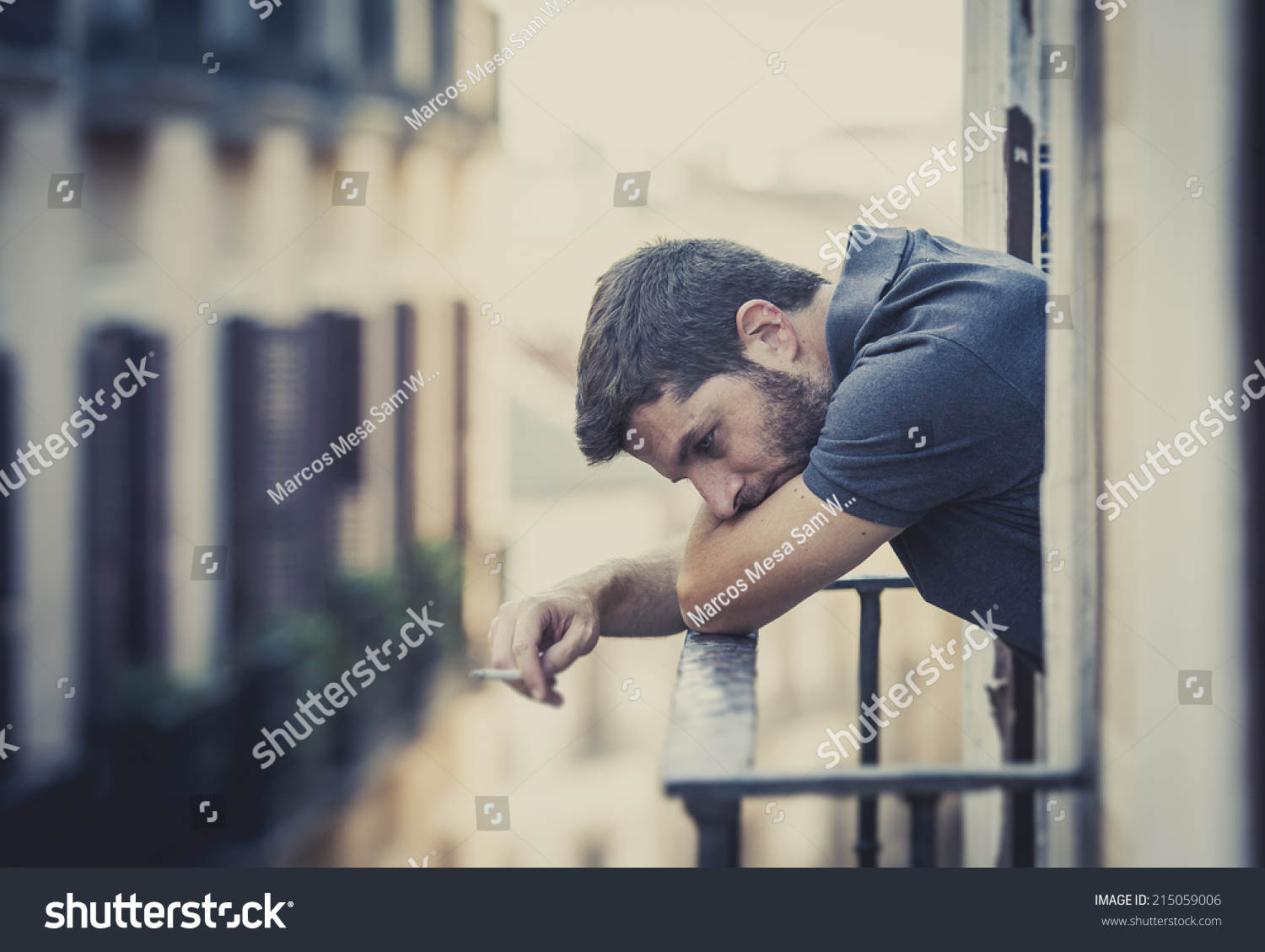Young man alone outside at house balcony terrace smoking depressed destroyed wasted and sad