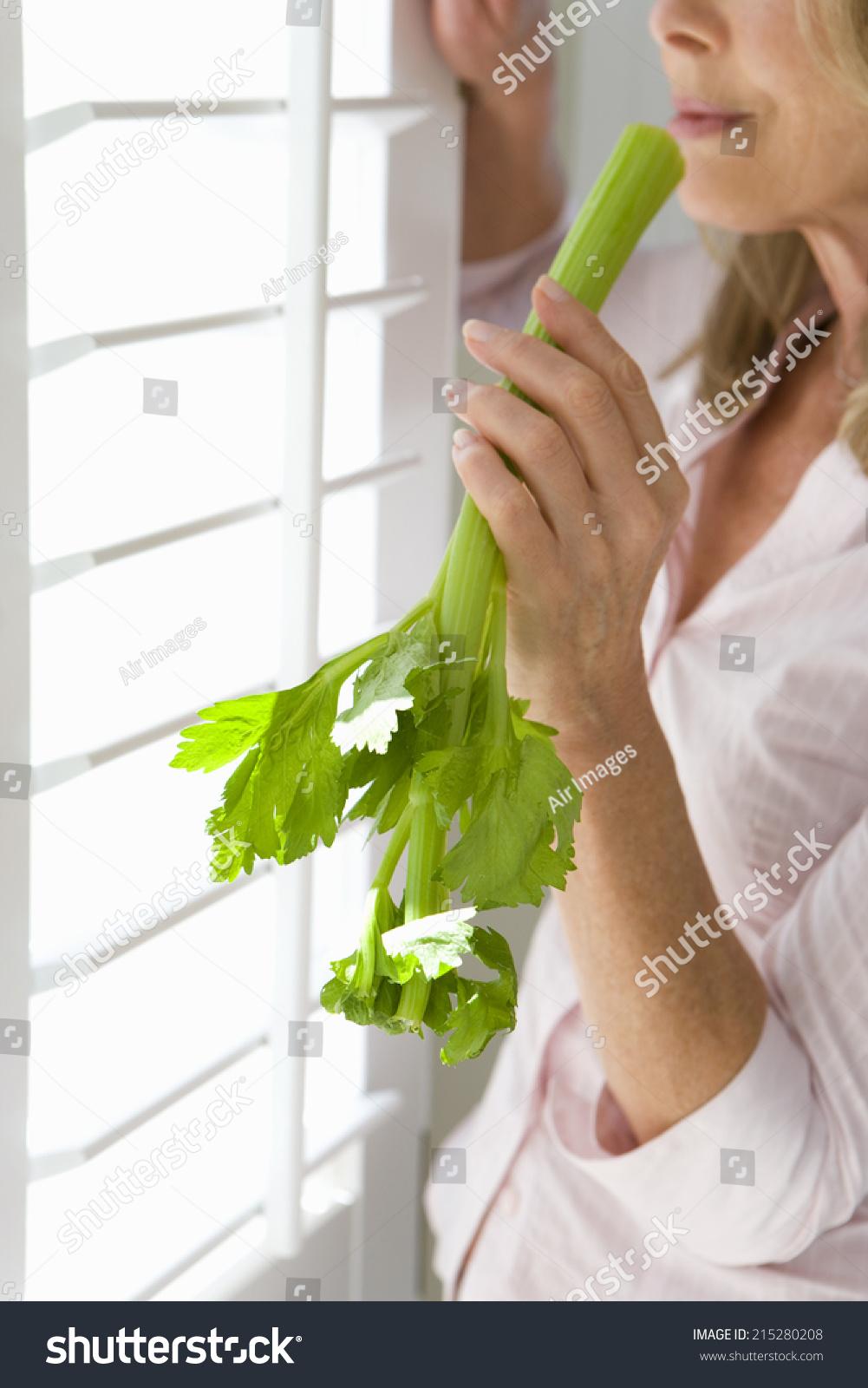 Mature Woman Holding Celery Stick Standing Stock Photo (Edit