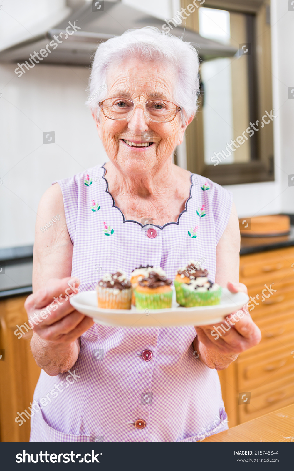 young beautiful woman decorating the little cupcakes with