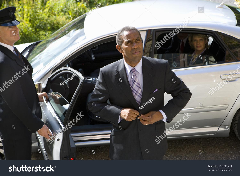 businessman doing up button of suit jacket chauffeur holding door of car open imagen de archivo. Black Bedroom Furniture Sets. Home Design Ideas