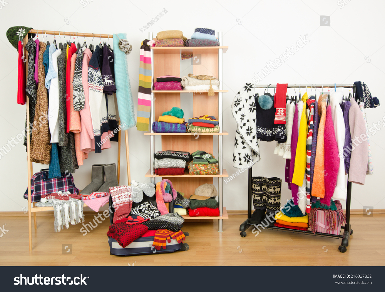 Packing The Suitcase For Winter Vacation. Wardrobe With Clothes Nicely  Arranged And A Full Luggage
