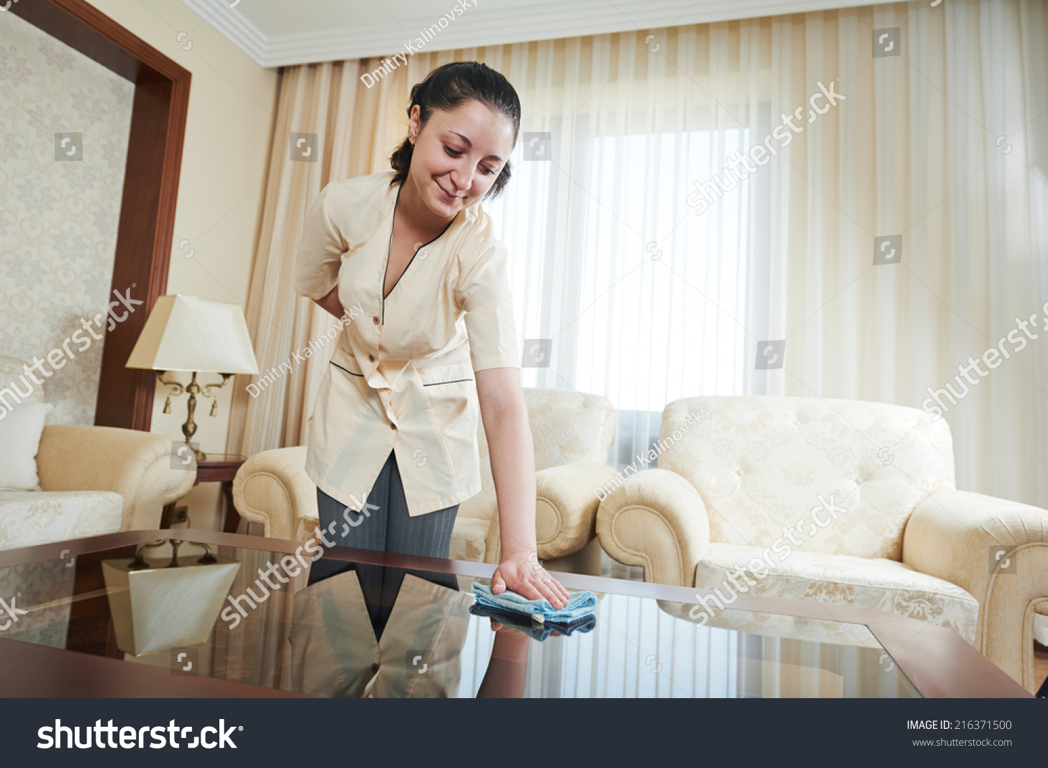 Hotel service. female housekeeping worker with cleaning table from dust in room #216371500