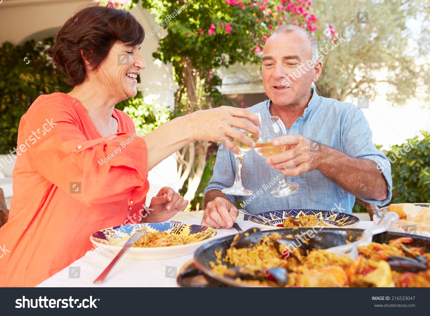 Mature hispanic couple enjoying outdoor meal stock photo for Meal outdoors