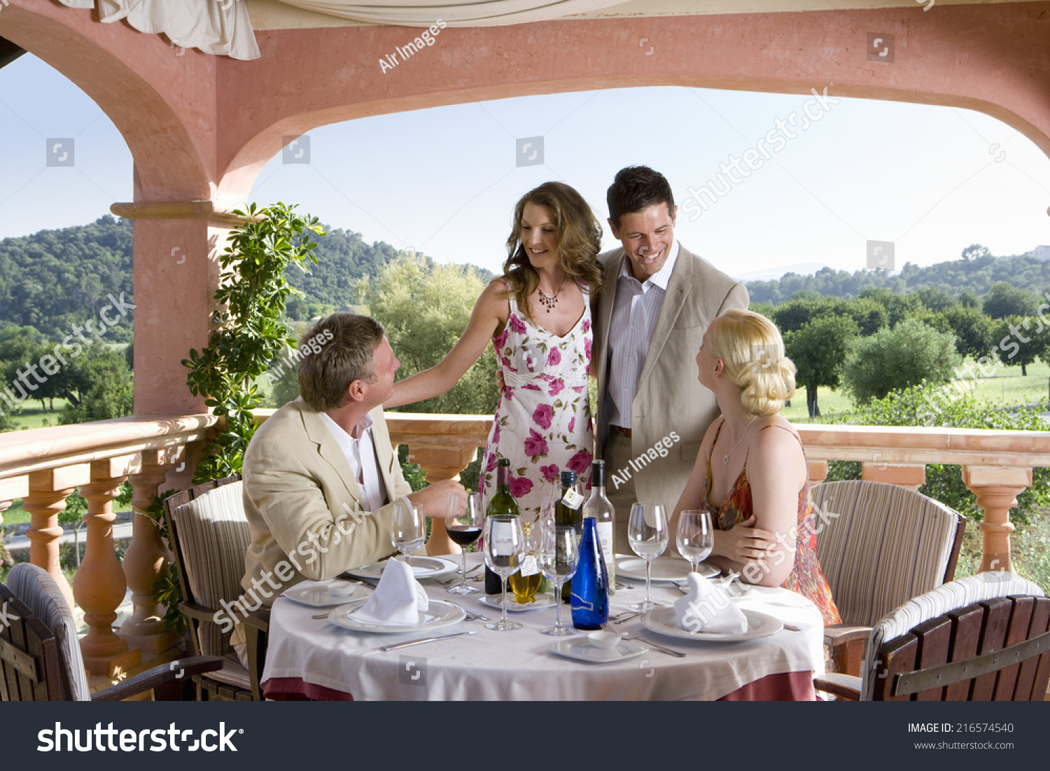 Welldressed couples drinking wine table on stock photo for Balcony restaurant group