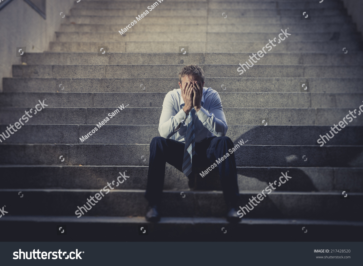 Young business man crying abandoned lost in depression sitting on ground street concrete stairs suffering emotional pain sadness looking sick in grunge lighting
