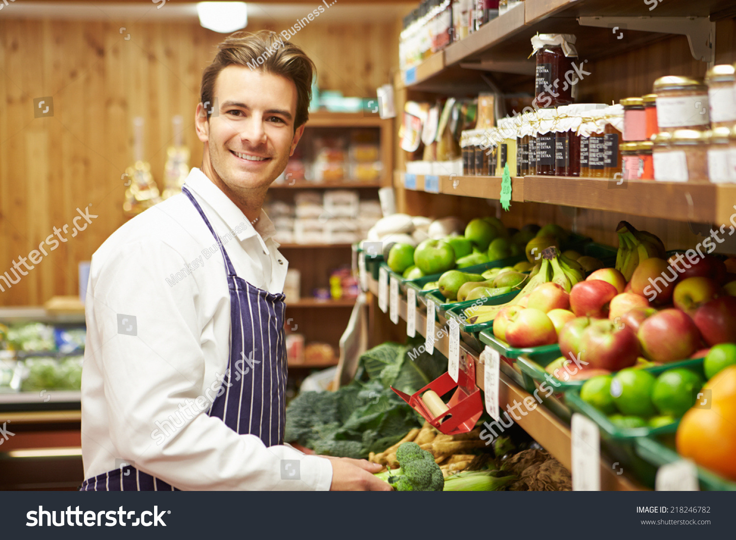 male s assistant at vegetable counter of farm shop stock photo save to a lightbox