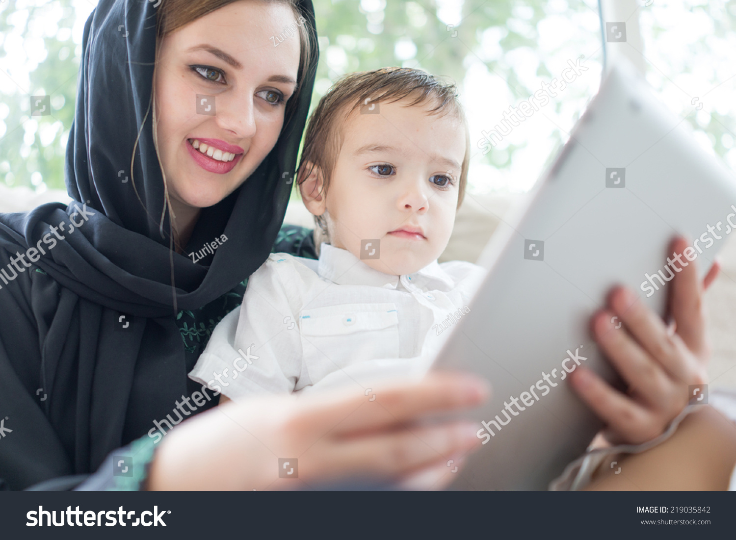 Beautiful arabic family mother and cute baby with tablet