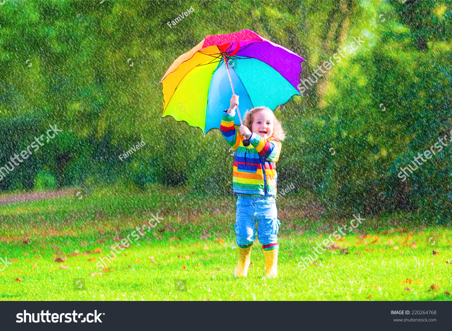 Funny cute curly toddler girl wearing yellow waterproof coat and boots  holding colorful umbrella playing in cf34034ad79e