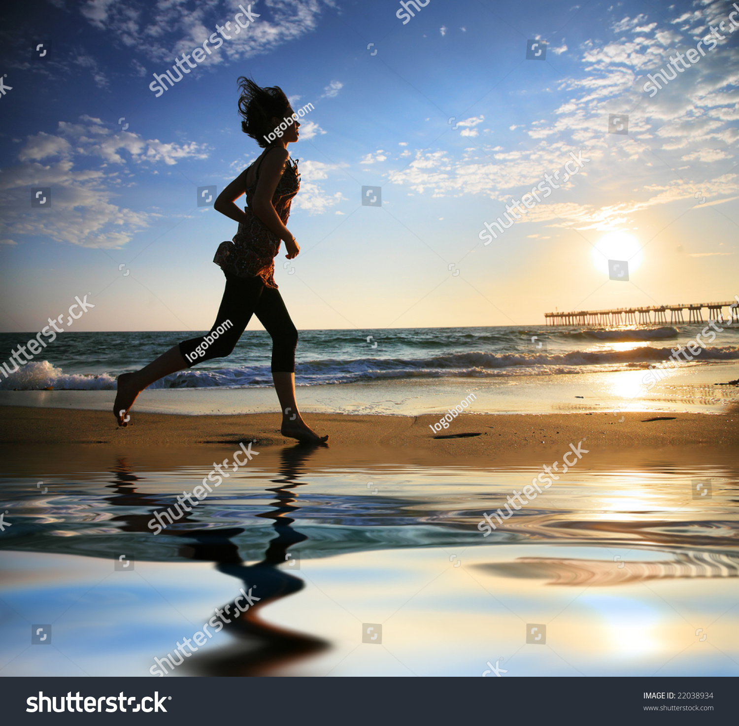 Woman Running By The Ocean Beach At Sunset Stock Photo