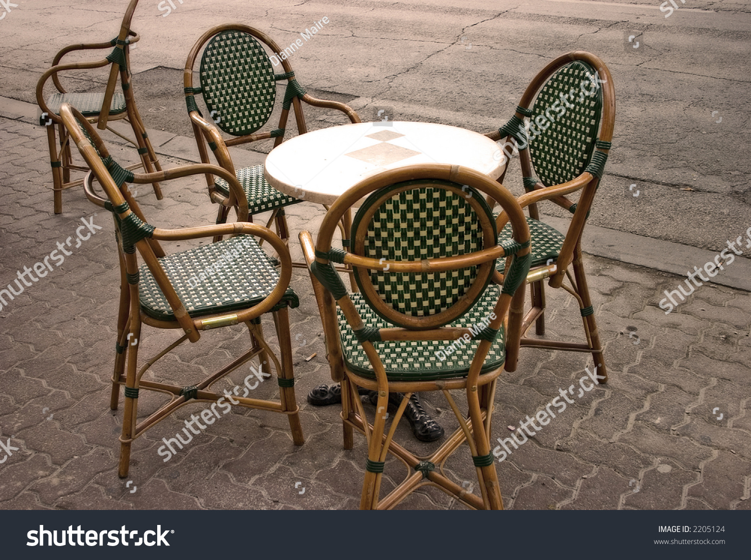 Cane Chairs Around A Small Round Table On An Empty Street.