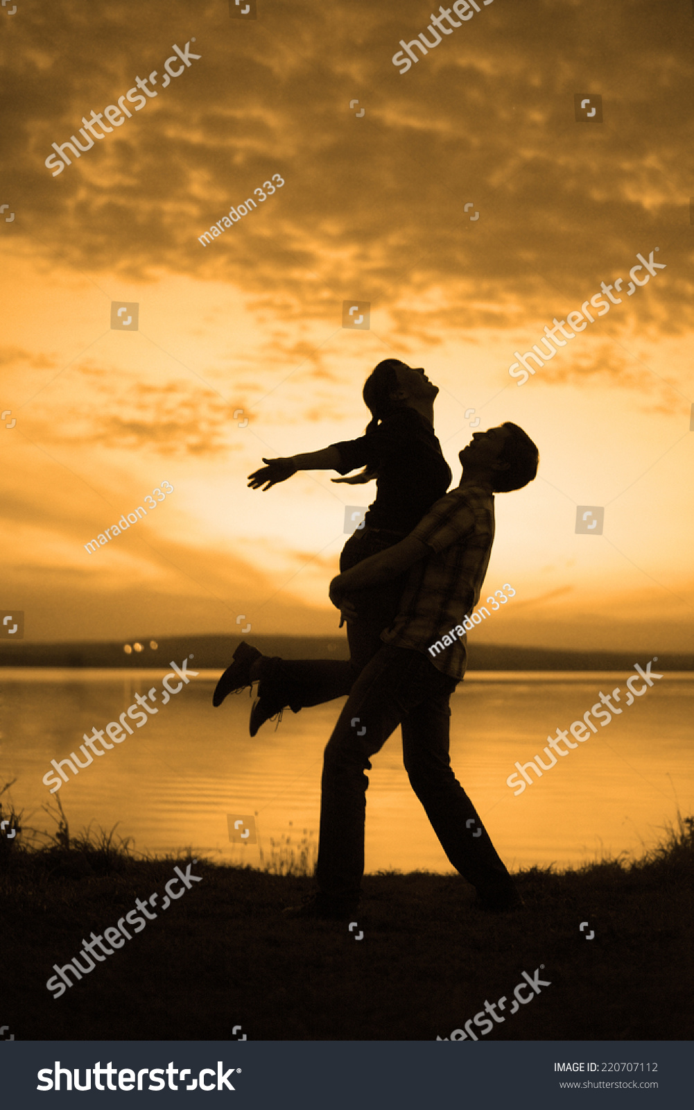 silhouette of couple man and woman jumping up holding hands and body against sunset sky with