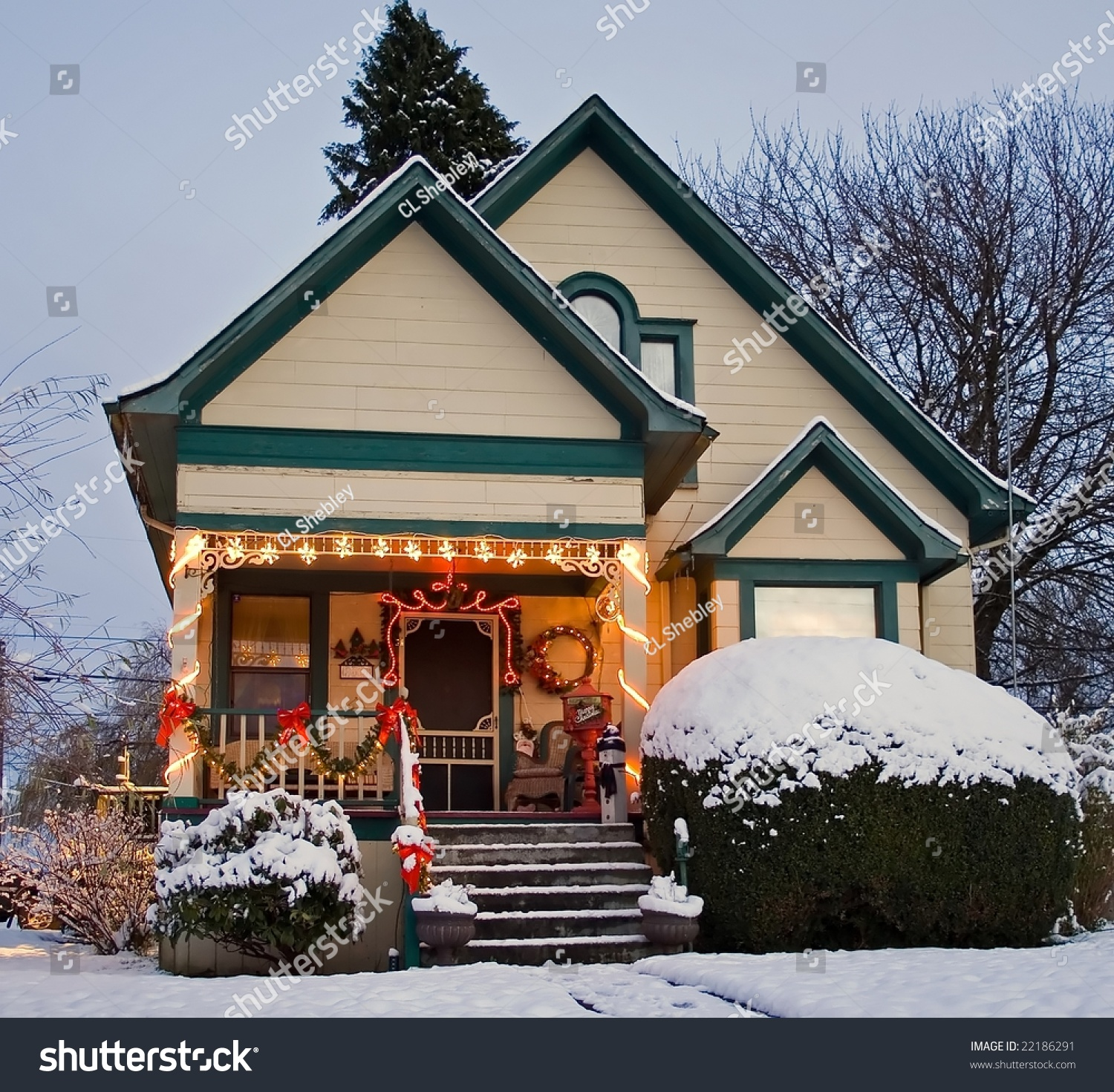 A Yellow Victorian House With Green Trim And Christmas