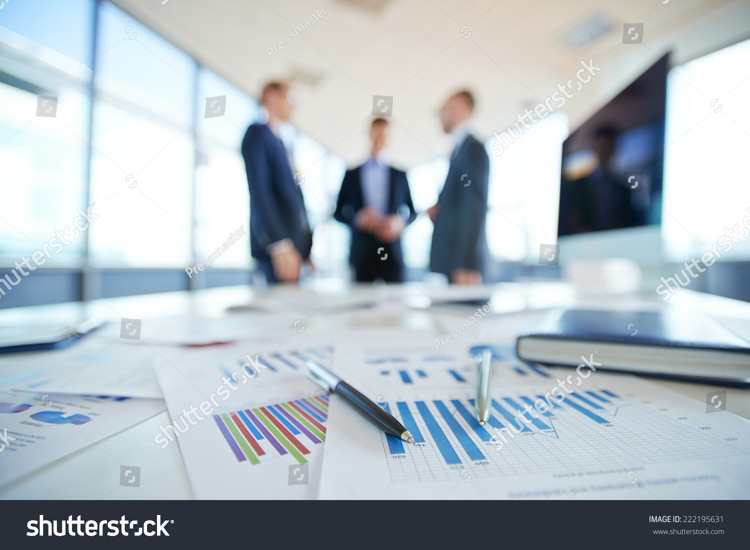 Documents On Office Table And Three Men Talking In The