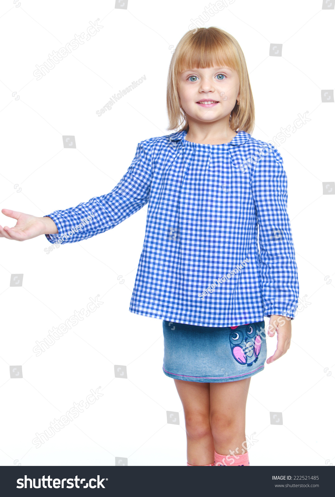 559fe25f910 Charming little girl in a blue blouse and denim skirt isolated on white  background