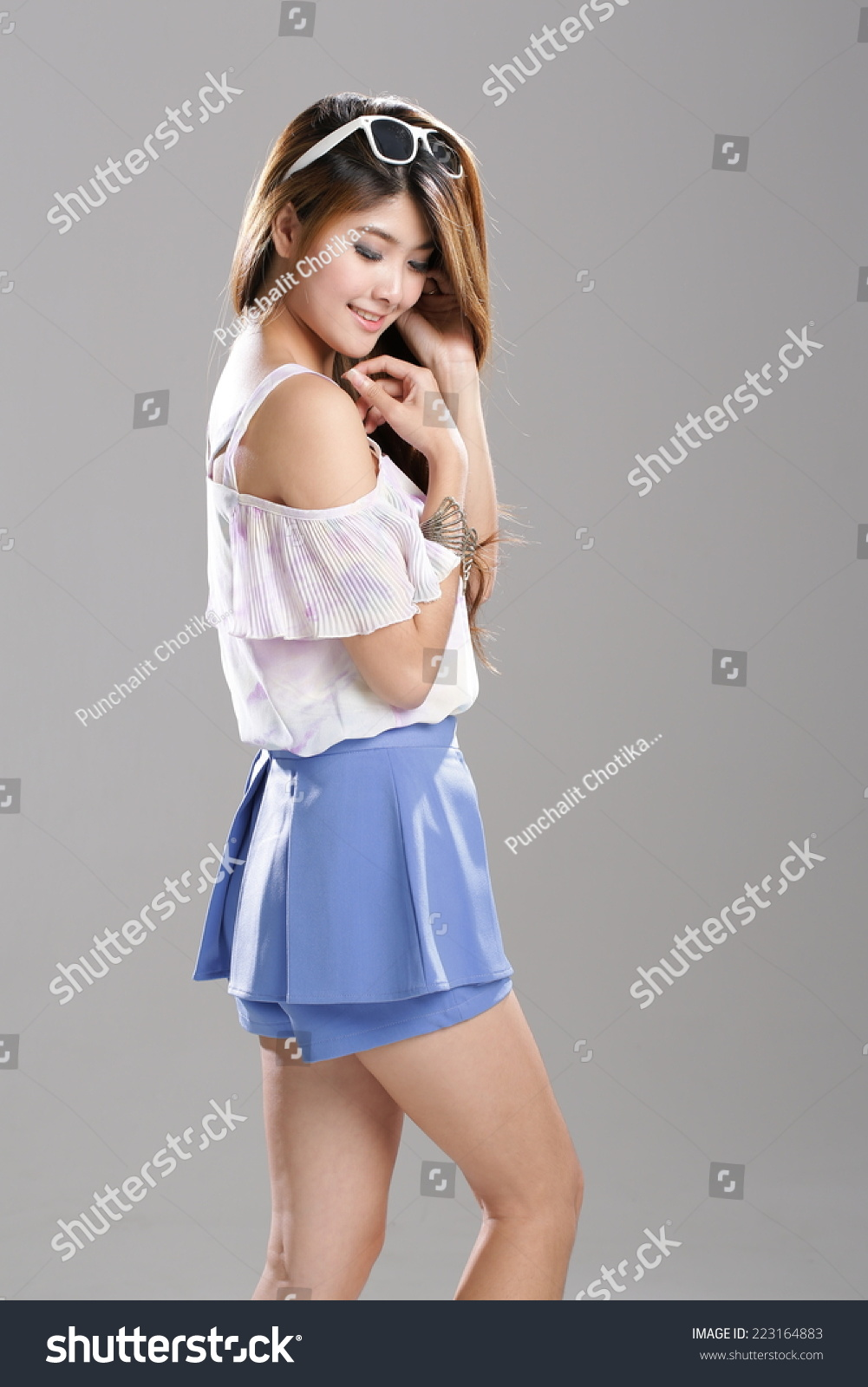 Asian Girl Posing In Sexy White Shade Lady Singlet Top With Blue Skirt Shorts