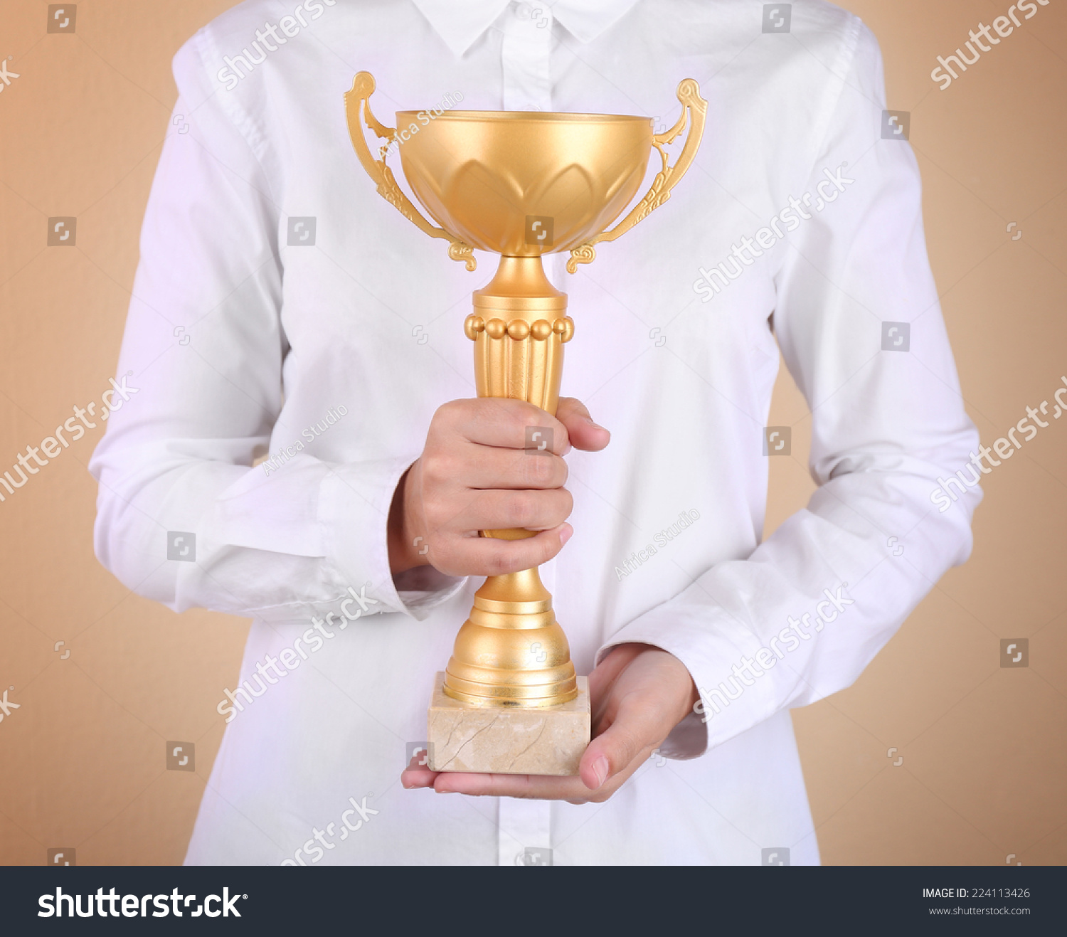 Woman holding trophy cup on color background #224113426
