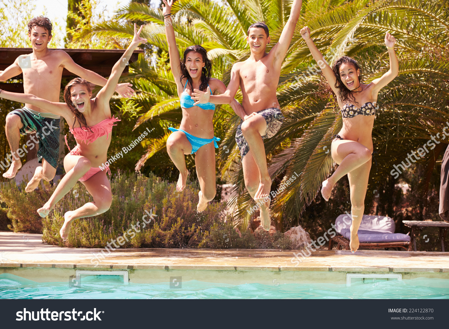 Group teenage friends jumping into swimming stock photo for Alor group piscine
