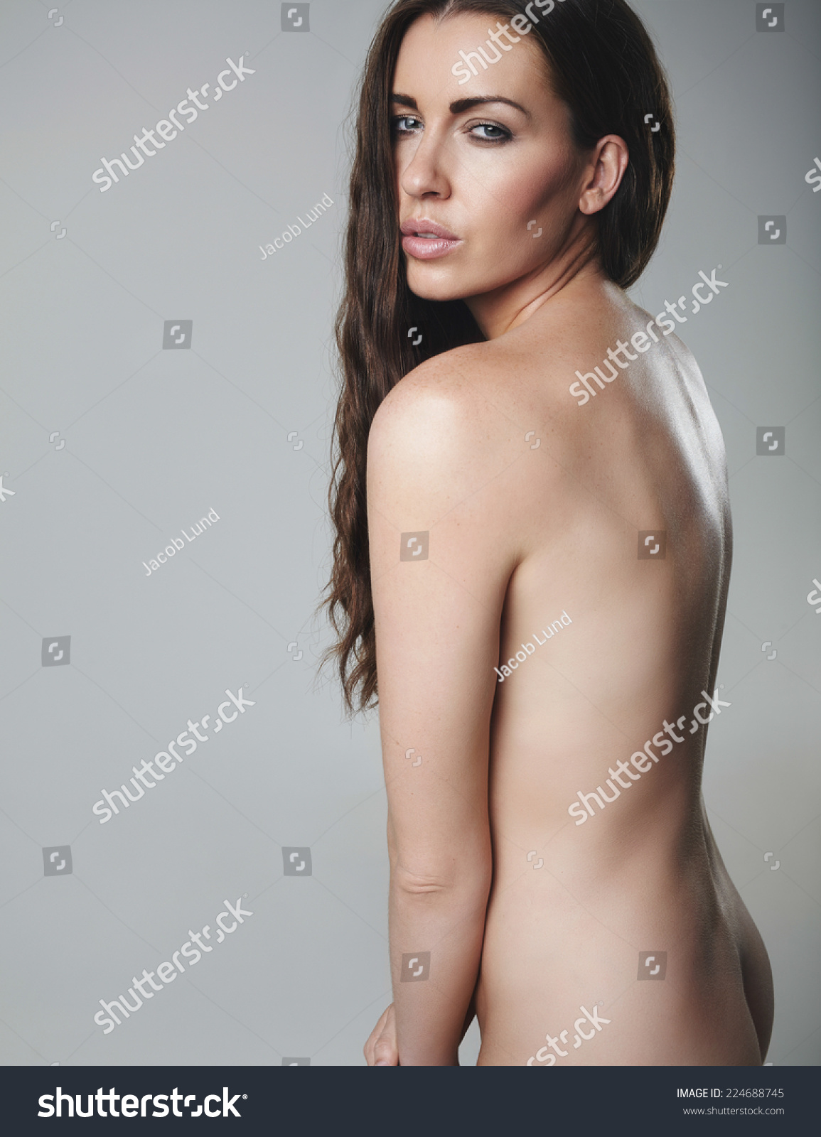young nude model Sexy young brunette posing naked. Nude female model on grey background.