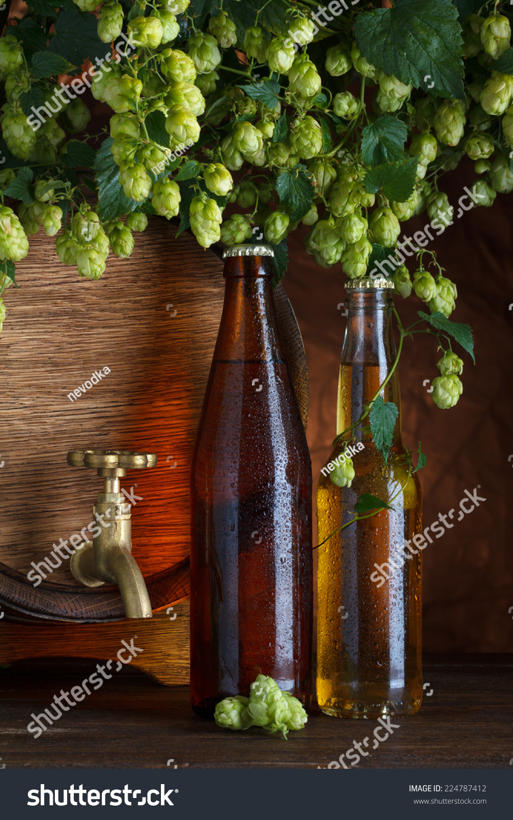 Beer bottles with beer barrel and fresh hops frame still for Beer bottle picture frame