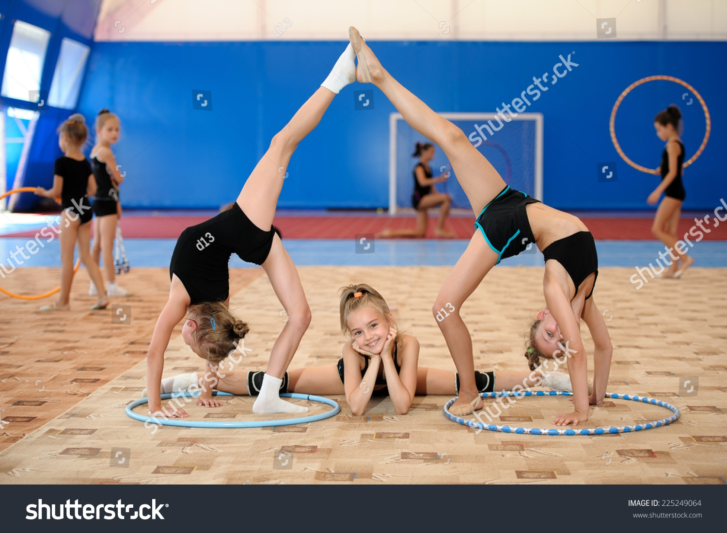 preteen stretch Girl doing leg-split between two ones stretching legs up