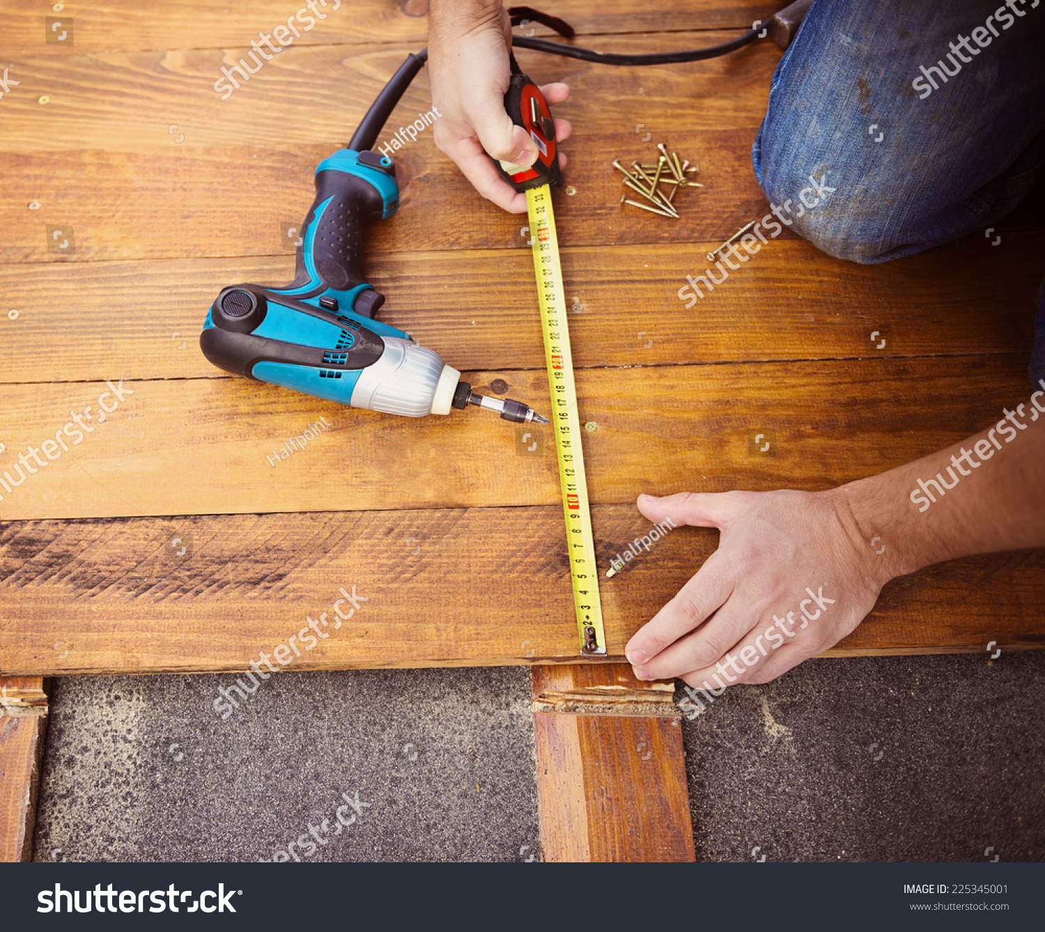 Close Up Of Male Hands Measuring Wood Flooring With Tape Measure