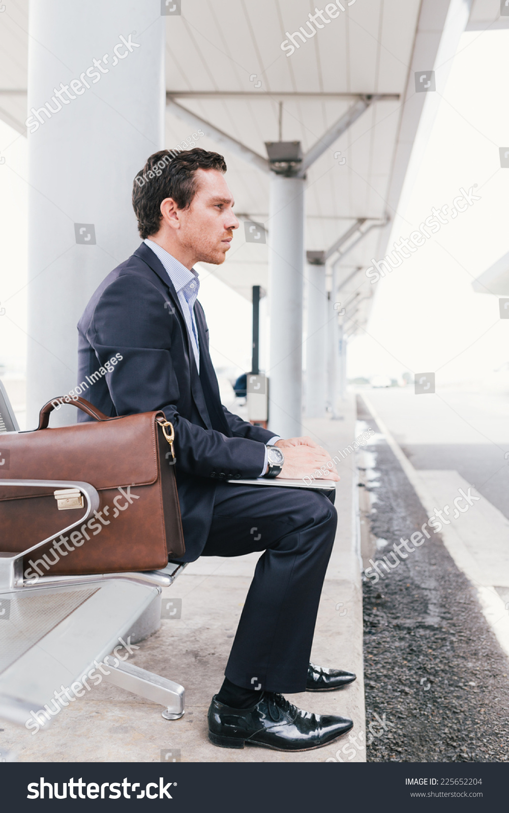 Man sitting in chair side - Businessman Sitting On The Chair At The Bus Station Side View