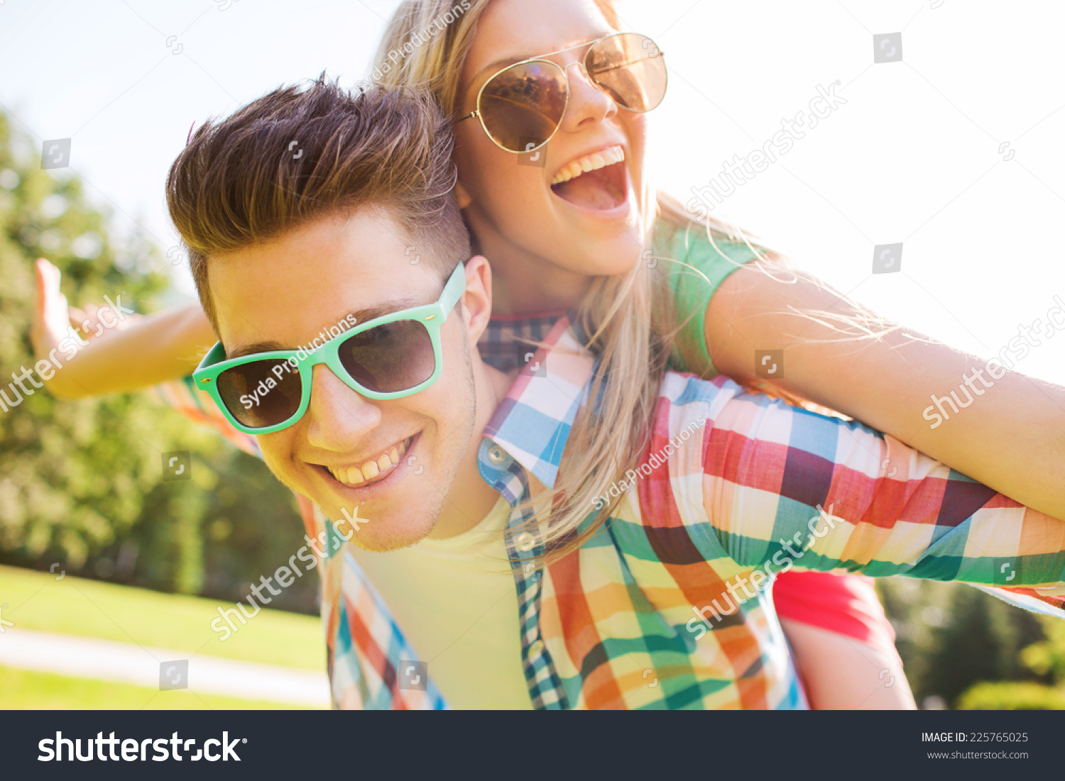 holidays, vacation, love and friendship concept - smiling teen couple in sunglasses having fun in summer park #225765025