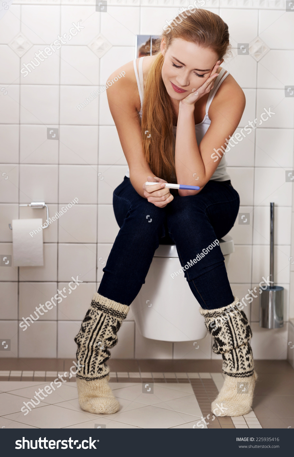 Portrait Of A Young Woman Sitting On A Toilet High-Res