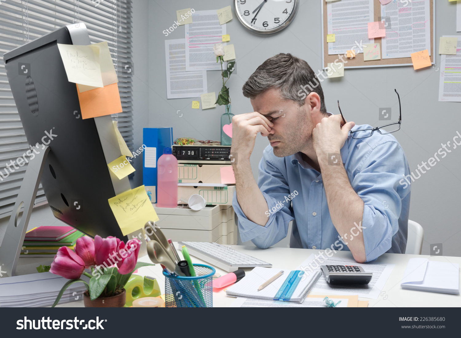 Frustrated office worker on the phone holding stock photo image - Depressed Bored Office Worker At His Desk Holding Glasses