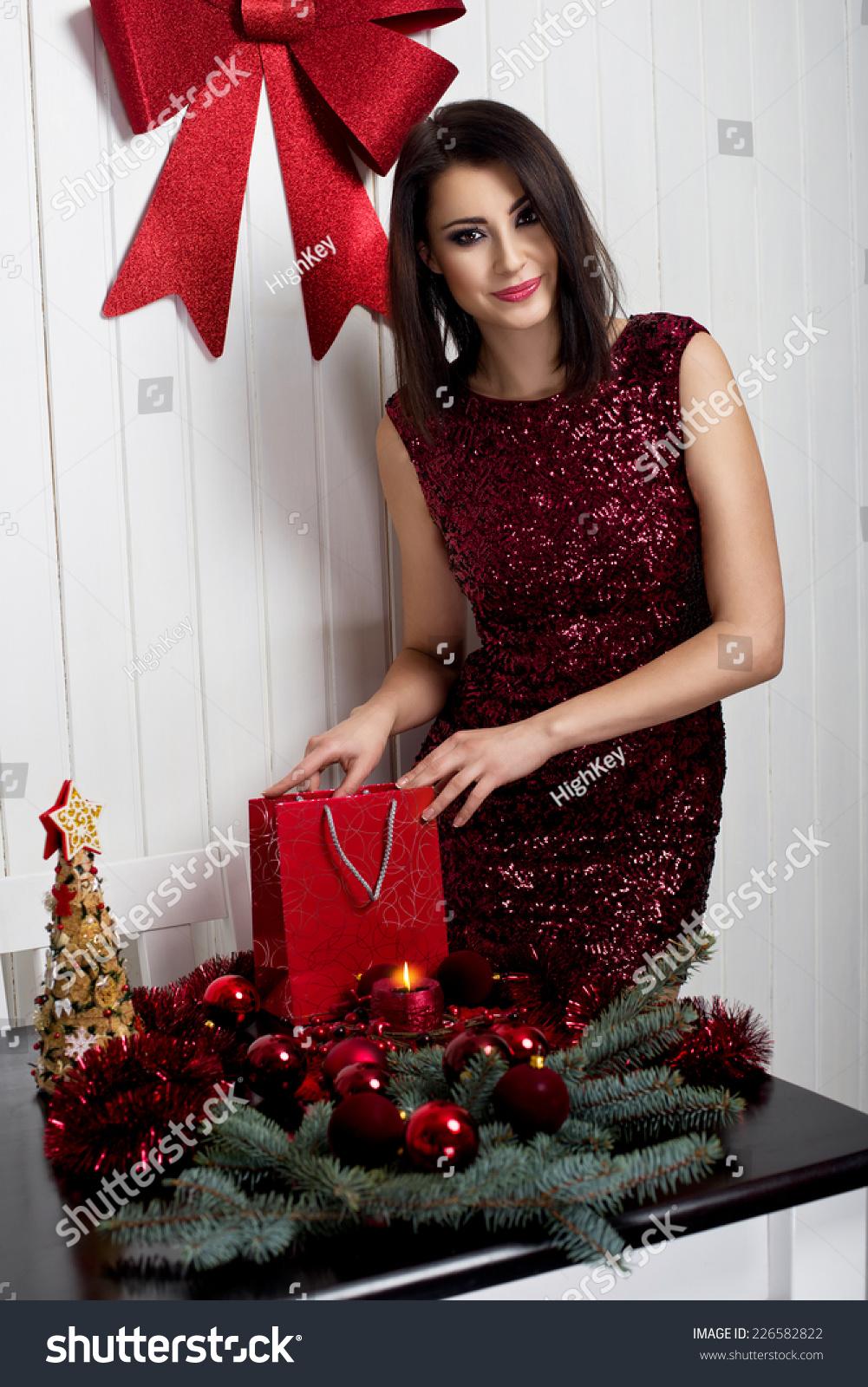 beautiful sexy christmas woman wearing glitter dress holding christmas present